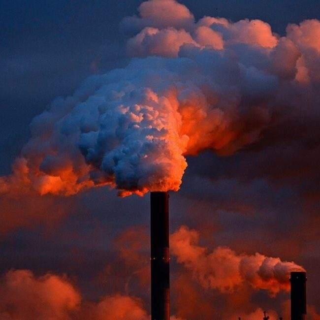 an industrial smoke stack emitting a large cloud of pollution at sunset